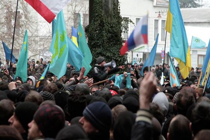 В настоящее время площадь перед зданием администрации полностью заполнена людьми, которые держат в руках российские флаги