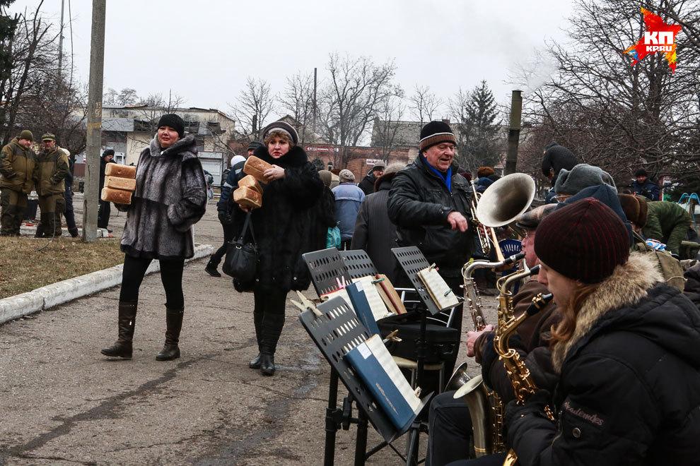 Городской оркестр играет на центральной площади в Дебальцево. Тут же люди получают гуманитарную помощь и бесплатную еду. Фото: Нигина БЕРОЕВА
