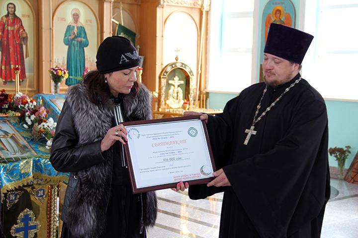 Сертификат на получение денег главе фонда Help the Children-SKD Елене Коневой вручил отец Андрей.