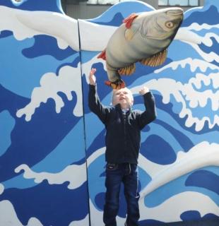 мальчик подбрасывает плюшевую рыбу