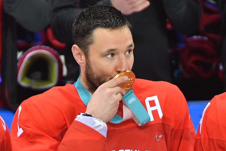Илья Ковальчук целует золотую олимпийскую медаль.
