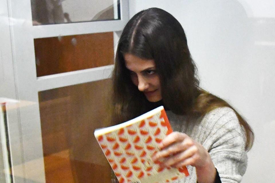 В «клетке» с пуленепробиваемыми стёклами Дария поначалу прячет лицо от камер за какой-то тетрадкой