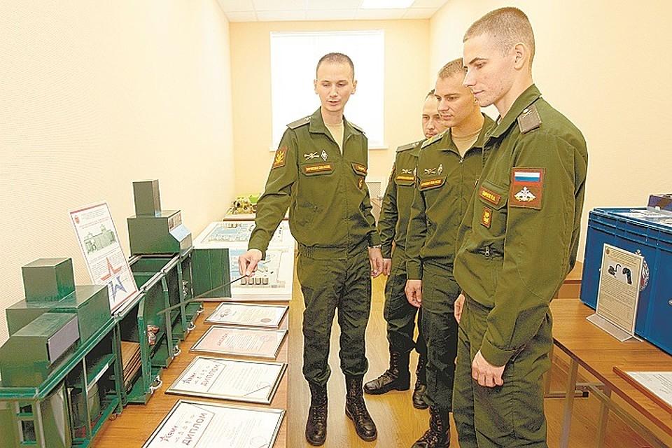 Бойцы показывают модель своей разработки: мобильного завода по переработке отходов.