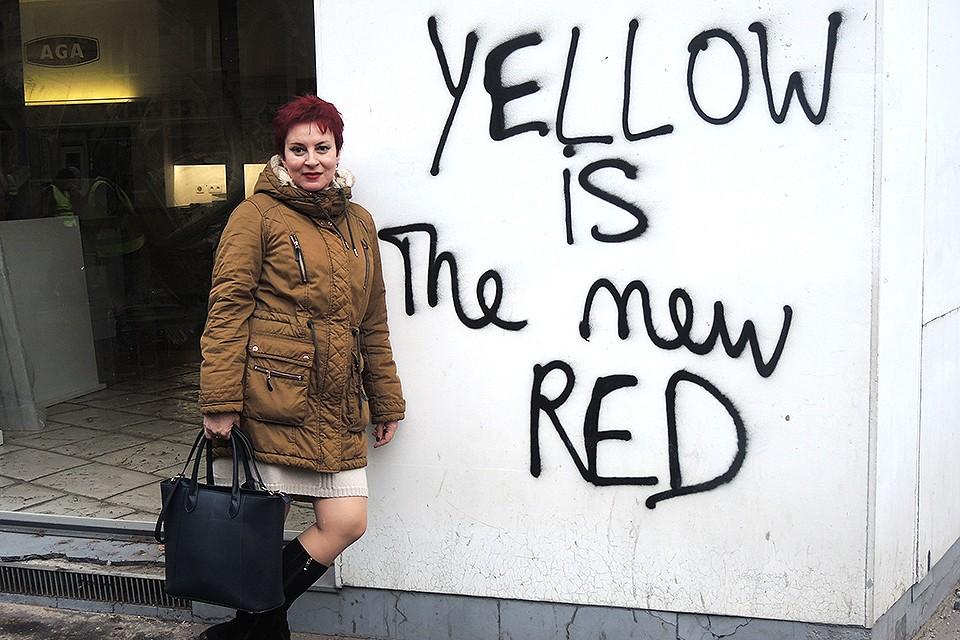 """Спецкор """"Комсомольской правды"""" Дарья Асламова в мятежном Париже. Надпись на стене: """"Желтый - это новый красный""""."""