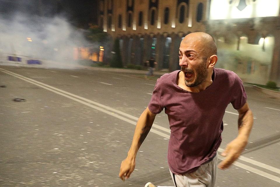 Участник уличных протестов у здания парламента в Тбилиси.