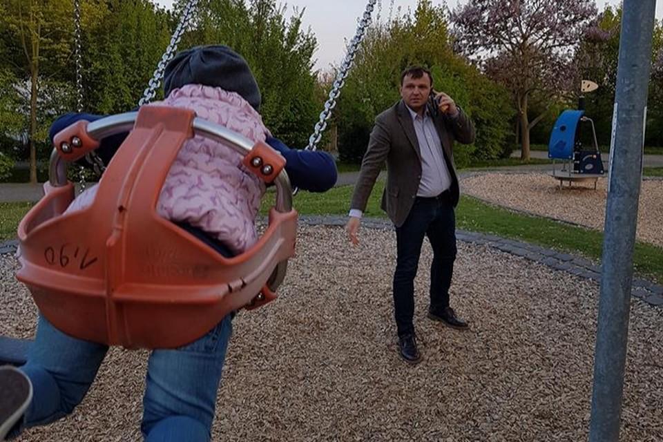 Андрей Нэстасе качает дочь на качелях в Германии.