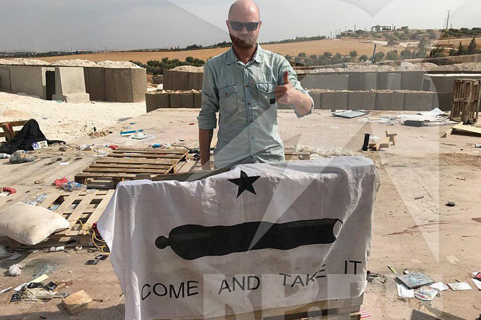 """Александр Коц с флагом, на котором написан девиз Центрального командования специальными операциями США - """"Приди и возьми"""""""