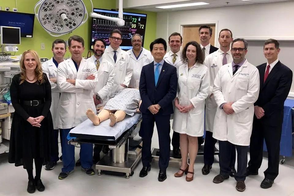 Хирурги, которые провели уникальную операция. Пациент лежит на каталке между ними. Вместо ног - протезы. Фото: The New England Journal of Medicine