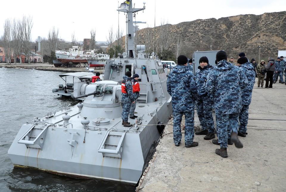 Украинские военные у возвращенного Россией катера в порту города Очаков.