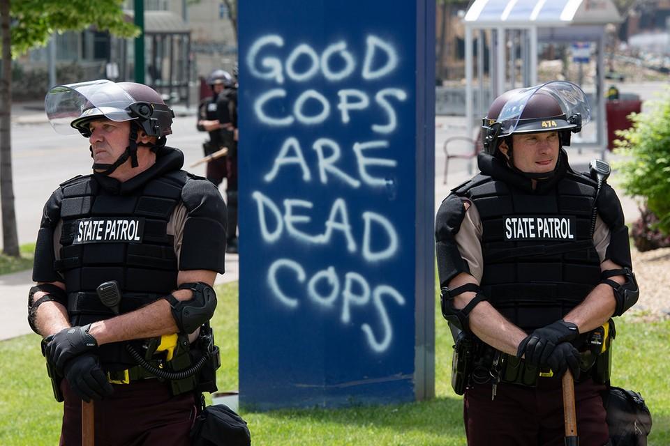 """Полицейские на улицах Калифорнии на фоне надписи """"Хорошие копы - мертвые копы""""."""