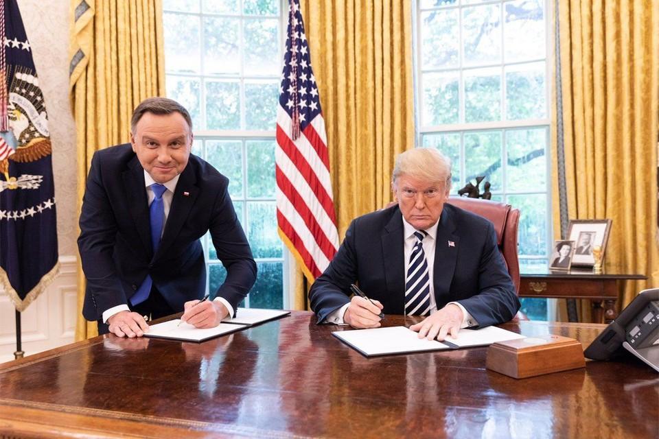 """Знаменитое фото из Белого дома, на котором Трамп по-хозяйски подписывает документ сидя, а президент Польши охотно проявляет гибкость """"партнера по НАТО"""". Фото: пресс-служба Белого дома"""