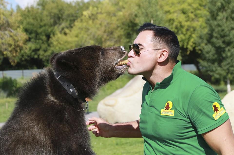 Сотрудник зоопарка Александр Чеботарев кормит мишку мороженым.