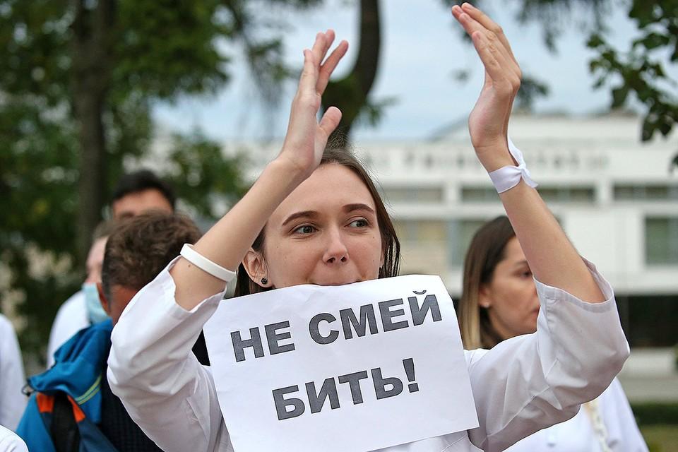 Участница акции медиков против насилия во время протестов у здания Белорусского государственного медицинского университета. Фото: Наталия Федосенко/ТАСС