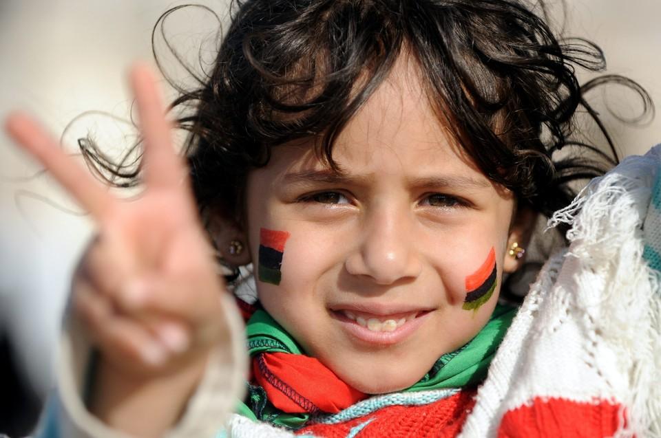 Бенгази, весна 2011 года. Девочка c флагами ливийской революции демонстрирует победный жест.