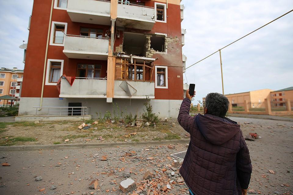 Мужчина фотографирует разрушения от обстрела в одном из сёл в районе боевых действий Карабахского конфликта.