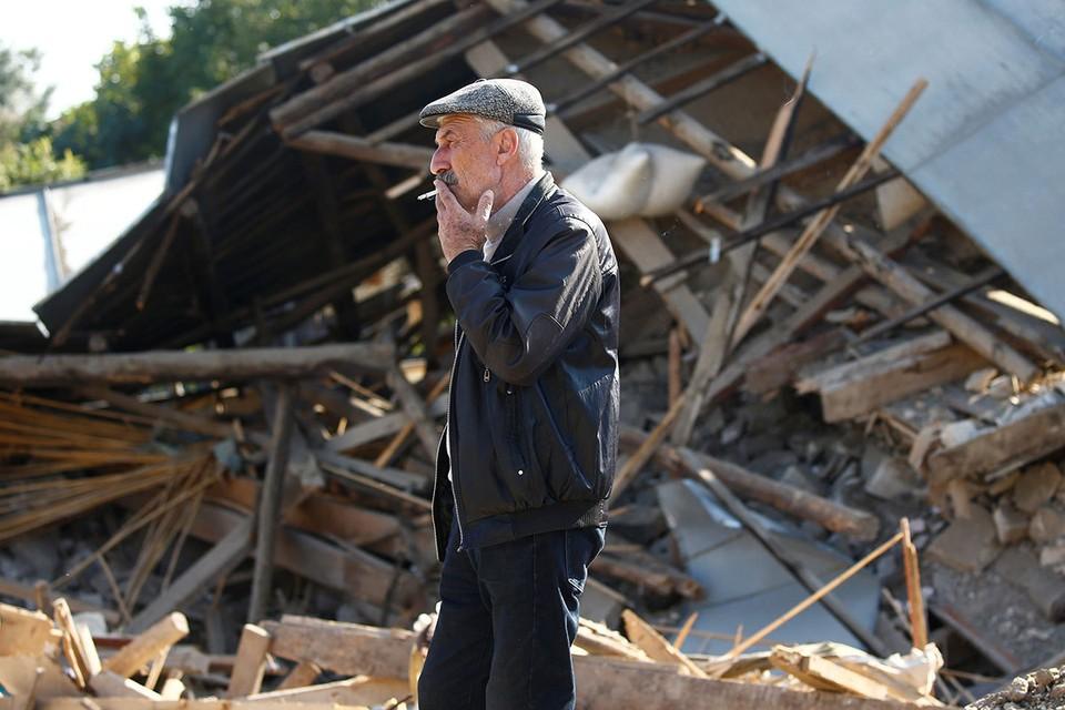 Житель города Мартуни, Нагорный Карабах, курит на фоне обломков разрушенного от обстрела дома.