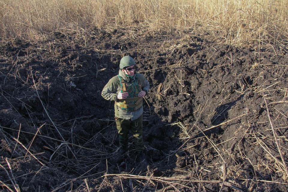 После обстрела поселка воронки остались в человеческий рост (на фото корреспондент «Комсомольской правды»)