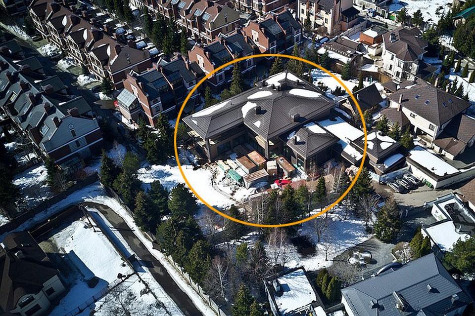 Одна из стен дома Собчак еще не достроена. Во дворе свалены стройматериалы. Рядом с коттеджем начали делать веранду. На парковке стоят машины строителей.