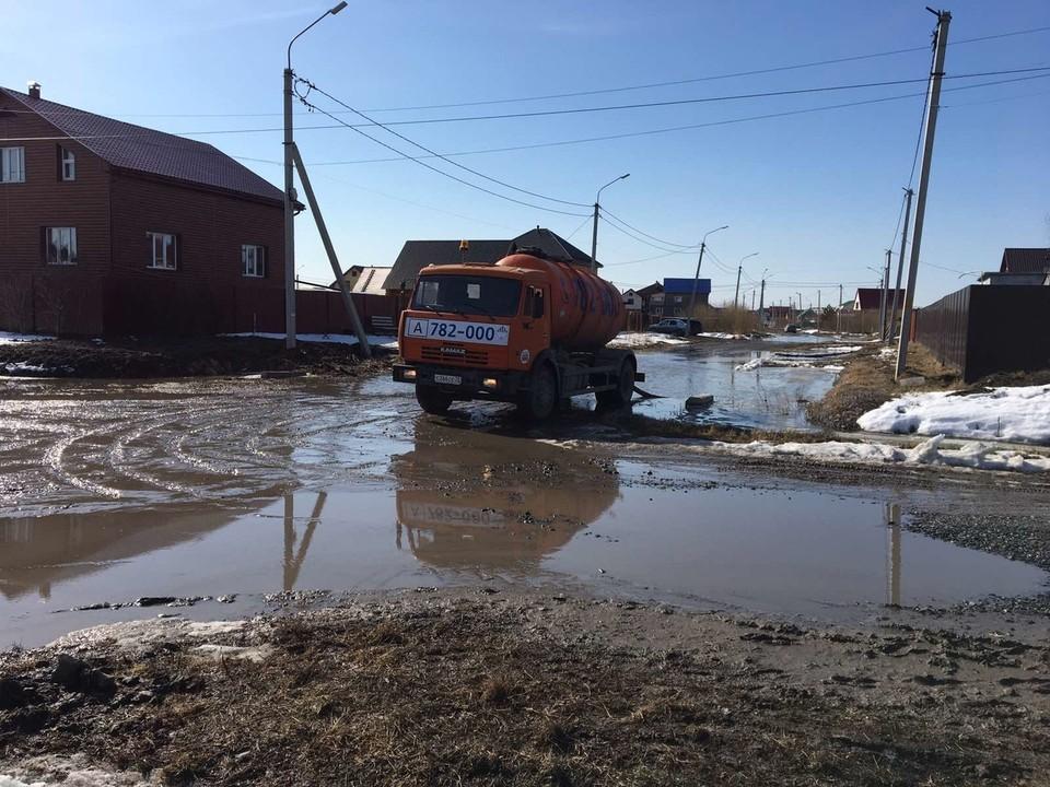 В тюменском Казарово спецмашины откачивают воду с затопленной дороги.