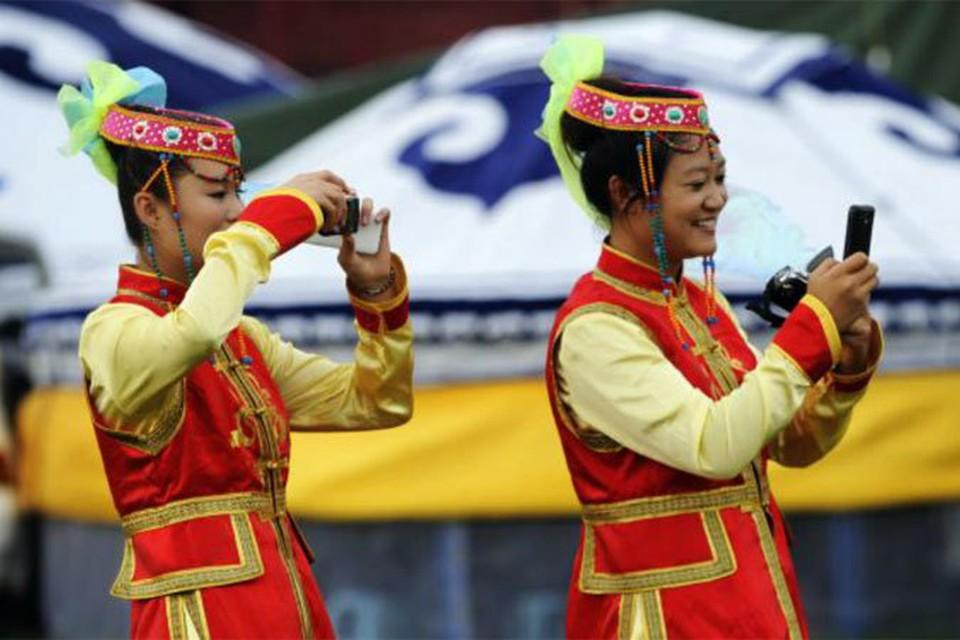 «Зато у нас у всех мобильники!» - с гордостью говорят защитники капитализма и демократии по-монгольски. На фото - девушки в монгольских национальных костюмах.