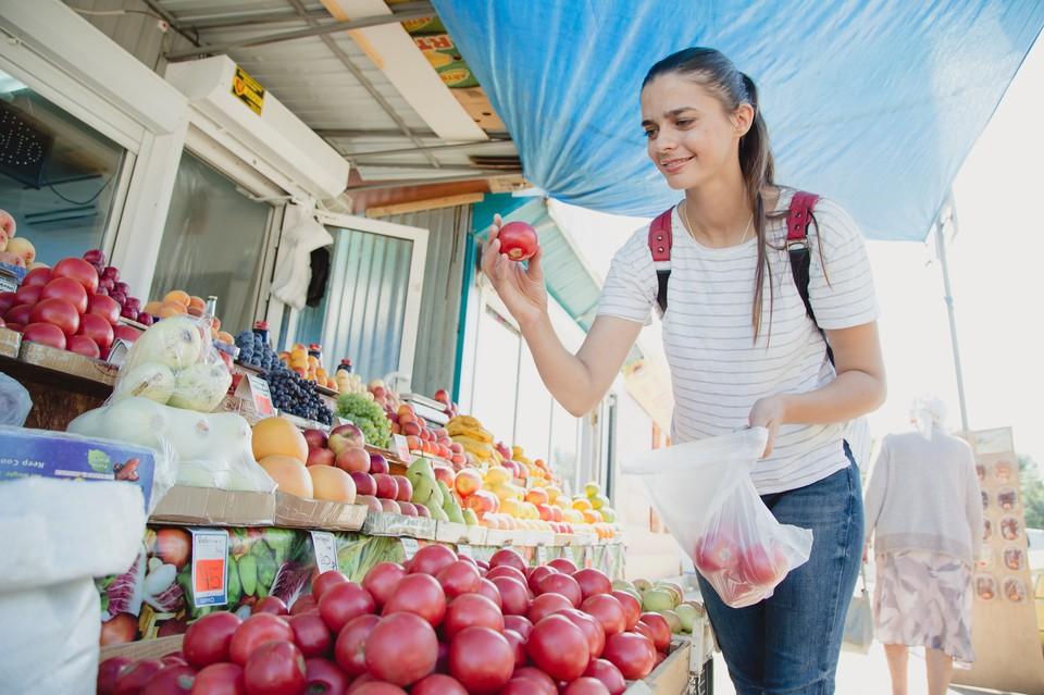 Девушка выбирает помидоры на рынке
