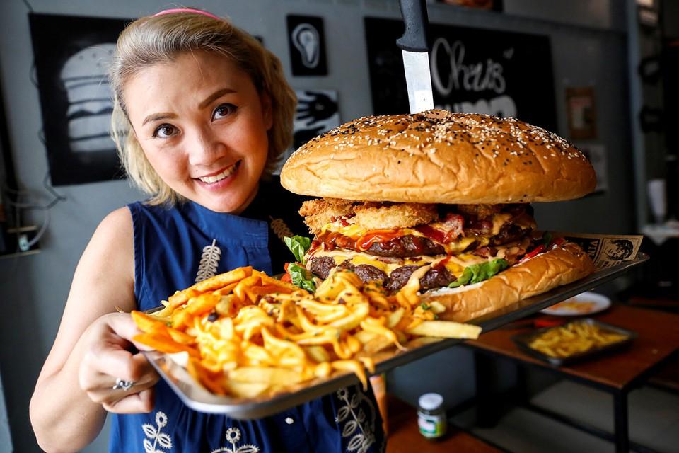 Официантка одного из кафе Бангкока готовится отнести гостю гигантский бургер. В заведении проводят чемпионат по поеданию этого блюда, вес которого достигает шести килограммов.