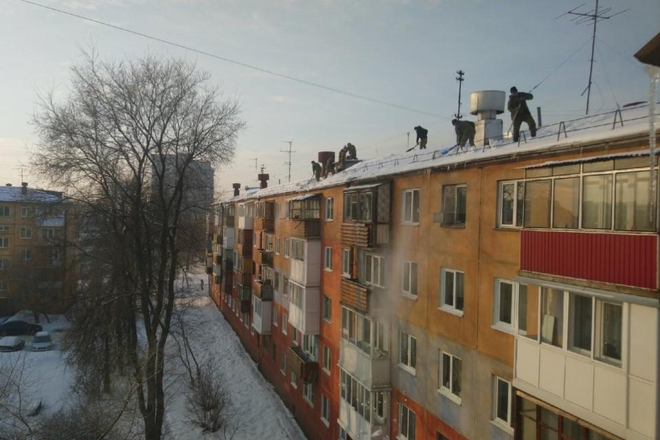 Рабочие сбрасывают снег с крыши кемеровской многоэтажки.
