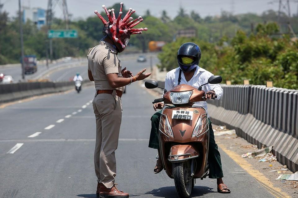 Индийский полицейский Раджеш Бабу носит шлем в форме коронавируса, чтобы убедить водителей оставаться дома во время 21-дневного общенационального карантина.