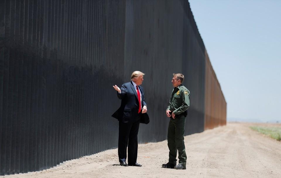 Президент США Дональд Трамп общается с сотрудником пограничной охраны во время посещения границы с Мексикой в штате Аризона.