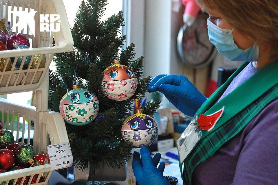 На фабрике ёлочных игрушек в Красноярске журналистам показали новинку - красивые шары ручной работы с рисунками защитных масок.
