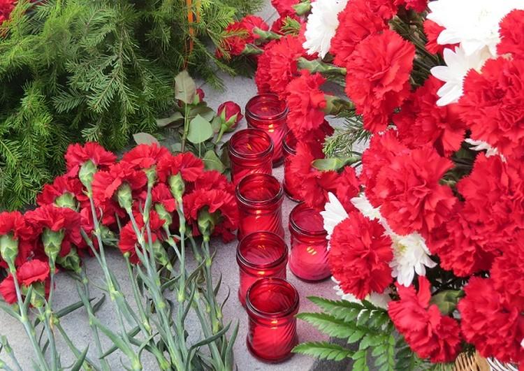 Цветы и свечи возле монумента