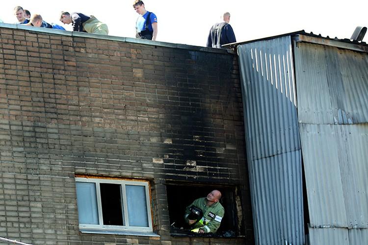 Сотрудники МЧС осматривают здание, в котором рано утром в субботу произошло возгорание. ФОТО Петр Зуев/ТАСС