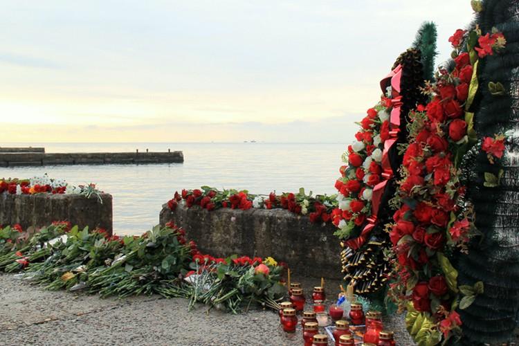 К берегу Черного моря все продолжают нести цветы и свечи в память о погибших...