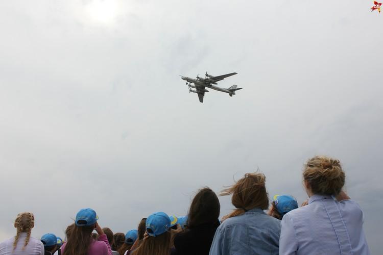 Будущие летчицы и взлетающий бомбардировщик.