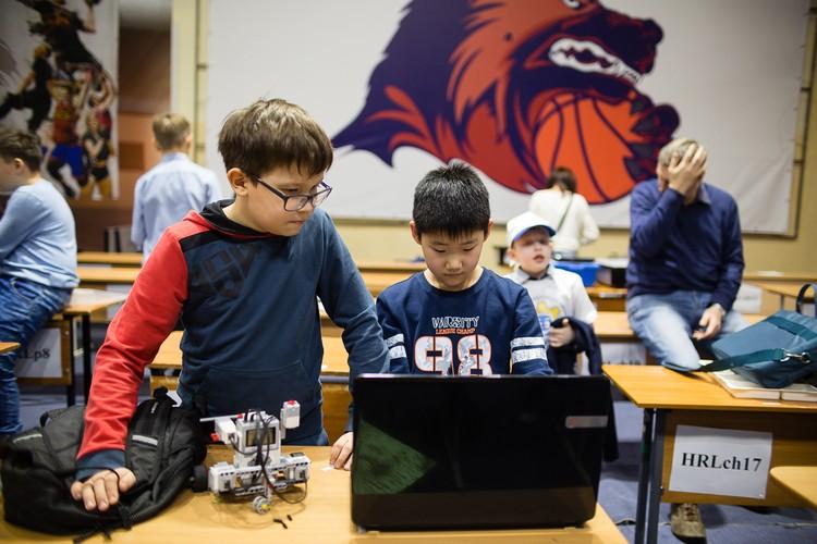 Школьники программируют своих роботов.