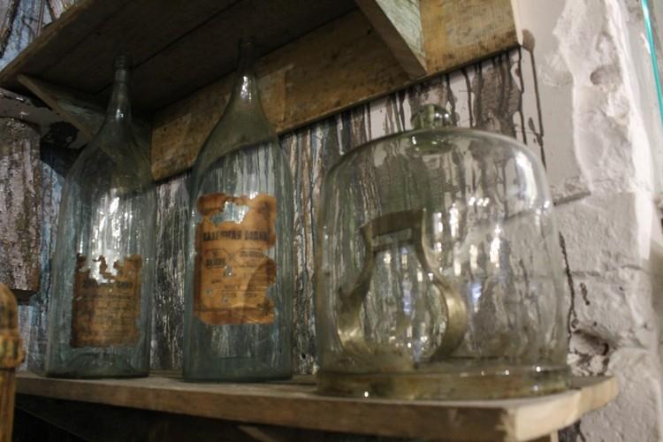 В экспозиции представлены самогонные аппараты различных размеров, старинные бутылки, деньги, стаканы, рюмки.