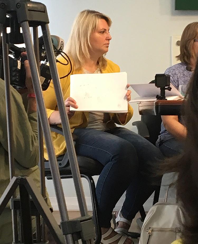 Мама Ани Павликовой показывает альбом, в котором дочь рисует пони за решеткой