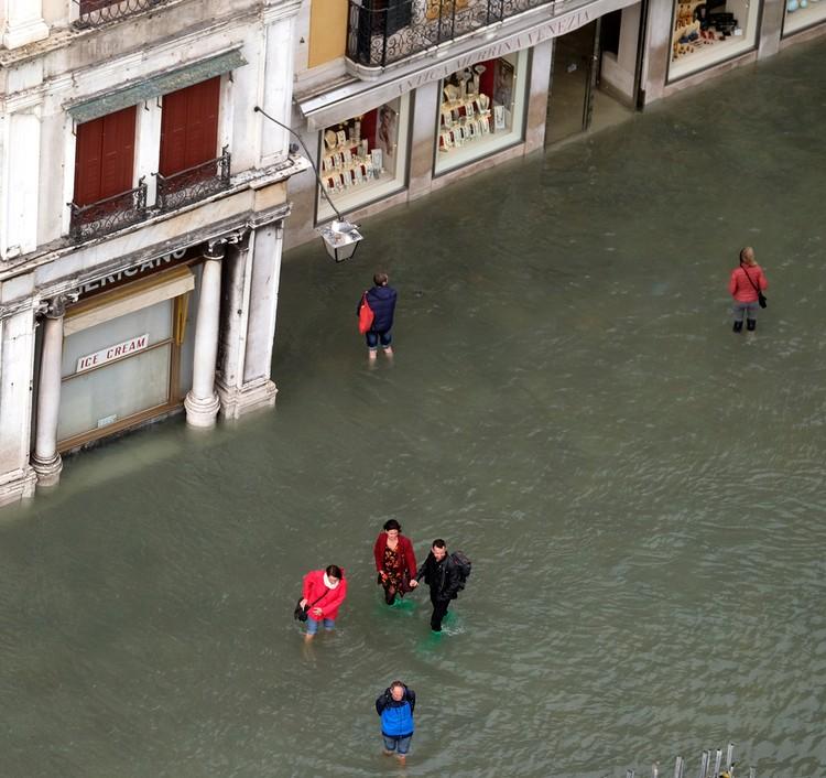 Туристы гуляют по площадям Венеции по колено в воде.