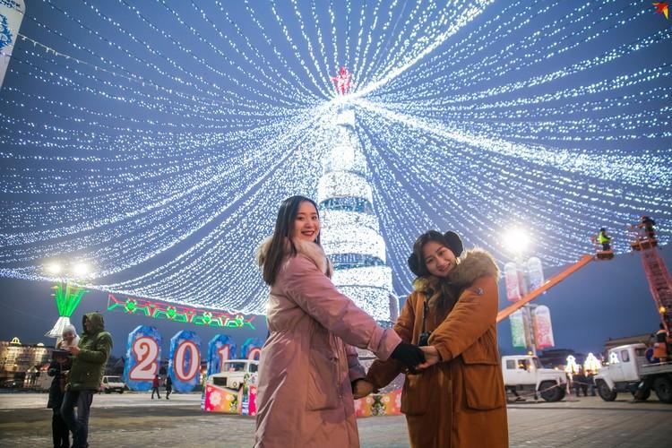 Иностранцы с удовольствием фотографируются у новогодней елки.