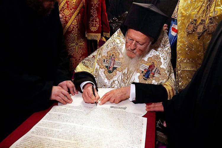 Патриарх Варфоломей ставит подпись на тексте томоса.