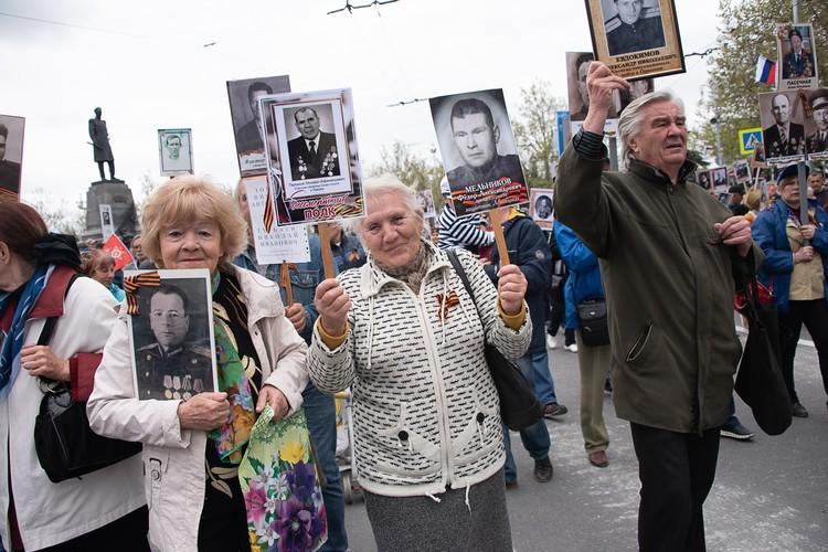 Жители и гости города приносят штендеры с портретами своих дедов и прадедов