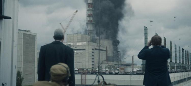 """Борис Щербина и Валерий Легасов наблюдают за вертолетом, стоя совсем рядом с четвертым энергоблоком. В реальности такого быть не могло. Фото: кадр из сериала """"Чернобыль"""""""