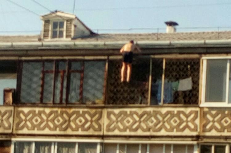 """Мужчина залезает по решетке, рискуя сорваться. Фото: группа """"Непростой Ангарск"""" ВКонтакте"""