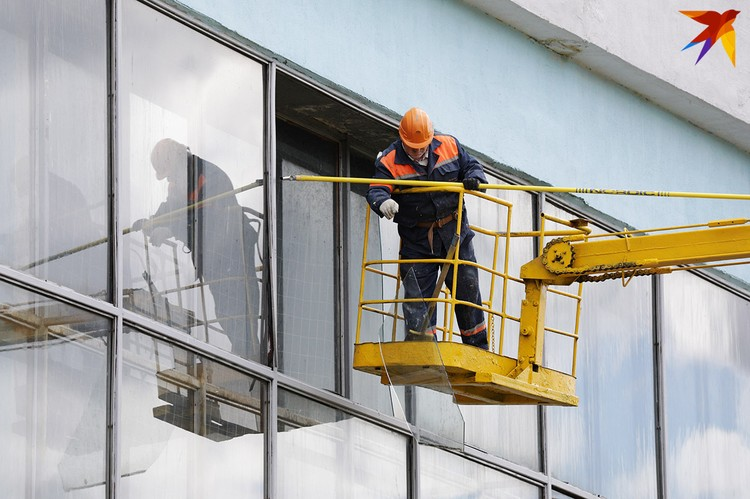 Рабочие демонтируют выбитое стекло.