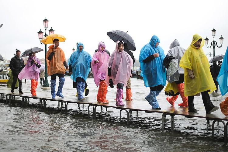 Tуристы наслаждаются прекрасным городом, несмотря на стихию