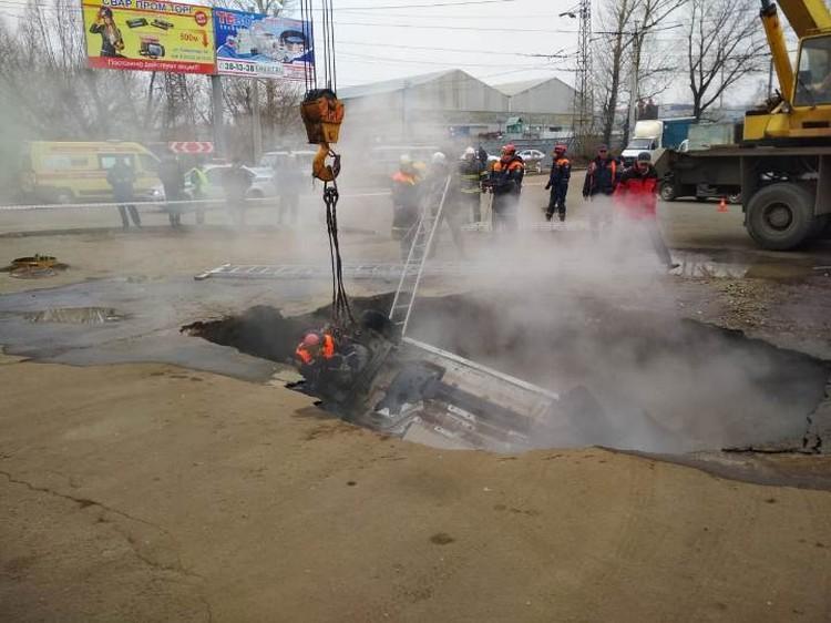 Машина упала в яму крышей вниз.