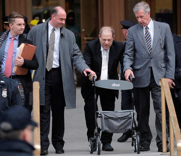 Харви Вайнштейн в окружении своих адвокатов покидает здание суда.
