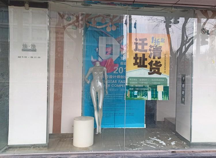 Голый манекен в закрытом магазине.