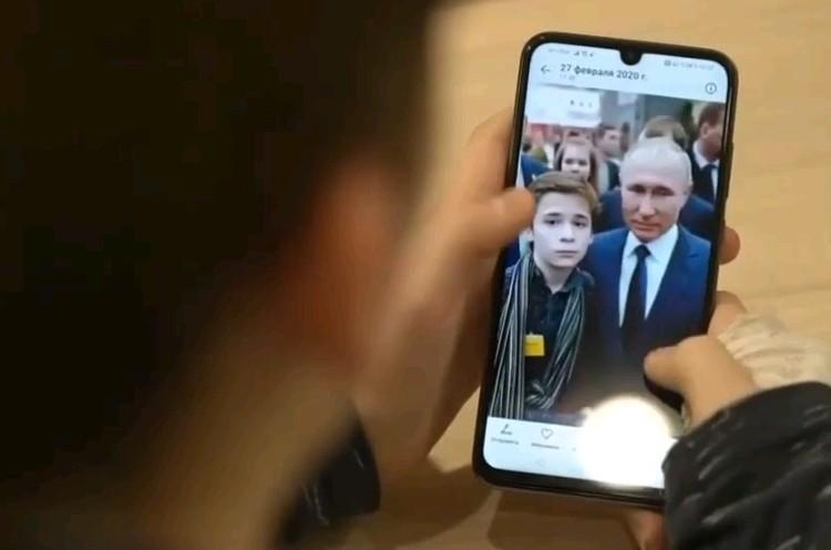 Миша рассматривает фотографии с президентом в своем смартфоне.