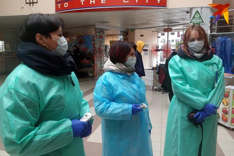 Сотрудники центра гигиены и эпидемиологии работают в защитных костюмах и масках.